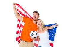 Upphetsade fotbollsfanpar som rymmer USA-flaggan Arkivbilder