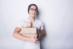Upphetsade innehavgåvor för ung man som isoleras på vit bakgrund arkivbild