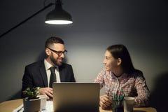 Upphetsade kollegor som ler bra företagsekonominyheter för utfrågning arkivbild