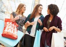 Upphetsade kvinnliga shoppare med Sale påsar i galleria Royaltyfri Foto