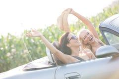 Upphetsade kvinnliga vänner som tycker om vägtur i cabriolet på solig dag arkivfoton
