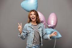 Upphetsade le innehavballonger för ung dam royaltyfria foton