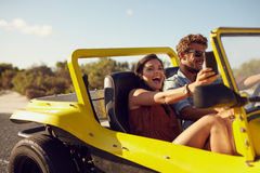 Upphetsade lyckliga par som tycker om på en vägtur Arkivfoton