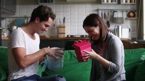 Upphetsade lyckliga unga par som hemma utbyter gåvor på ferie
