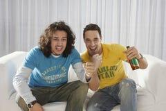 Upphetsade män som håller ögonen på television med ölflaskan Arkivfoton