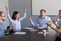 Upphetsade motiverade lagcoworkers som firar otrolig busine royaltyfria foton