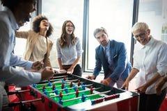 Upphetsade olika anställda som tycker om rolig aktivitet på arbetsavbrottet, idérik vänlig arbetarleklek arkivbild