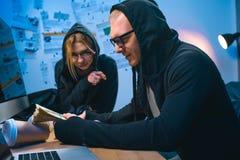 upphetsade par av en hacker med bunten av kassa royaltyfri fotografi
