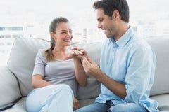 Upphetsade par som får förlovade på deras soffa Arkivfoton