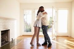 Upphetsade par som kramar i nytt hem på rörande dag Arkivbilder