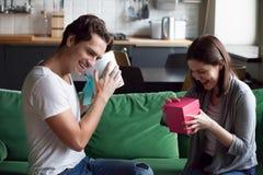 Upphetsade par som utbyter gåvor som öppnar askar med gåvor på H fotografering för bildbyråer