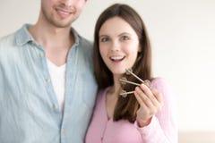 Upphetsade par som visar nya tangenter i fokusen, fastighetköp Arkivbild