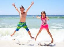 Upphetsade små barn som tillsammans hoppar på stranden Royaltyfria Foton