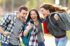Upphetsade studenter som mottar goda nyheter på telefonen arkivfoto