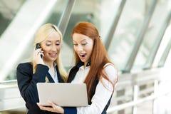 Upphetsade surpirsed affärskvinnor som mottar goda nyheter via email Arkivbild