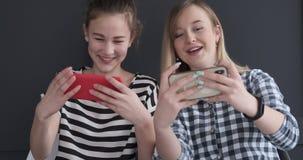 Upphetsade tonårs- flickor som spelar leken på mobiltelefoner arkivfilmer