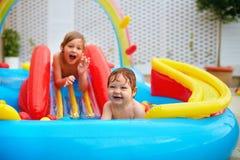 Upphetsade ungar, familj som har gyckel i färgrik uppblåsbar pöl på uteplats Royaltyfria Foton