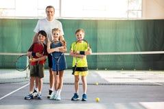 Upphetsade ungar och soffa som har gyckel på tennisbanan royaltyfri bild