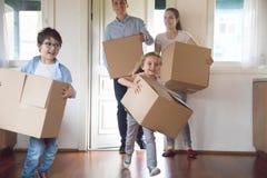 Upphetsade ungar som kör att bära, boxas flyttning till det nya huset royaltyfri bild