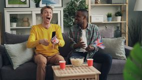 Upphetsade ungdomarstöttar hållande ögonen på sportar för brittiskt lag för att spela på TV- och vinkaflaggor av Storbritannien s stock video