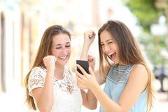 Upphetsade vänner som kontrollerar online-goda nyheter i en telefon arkivbilder