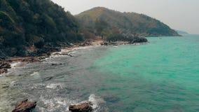 Upphetsande brun stenig kustlinje nära gröna skogsbrukkullar lager videofilmer