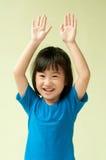 Upphetsat asiatiskt litet barn som lyfter hand upp två Arkivbilder