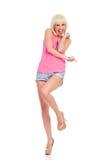 Upphetsat kvinnaanseende på ett ben och peka Royaltyfria Bilder