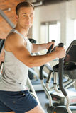 Upping my cardio. Handsome young man doing cardio exercise on step machine and smiling Stock Images