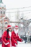 Uppklädden för unga kvinnor som santas deltar i välgörenhethändelsen Stockholm Santa Run i Sverige Royaltyfri Foto