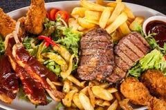 Uppläggningsfat av blandade kött, sallad och pommes frites Royaltyfri Bild