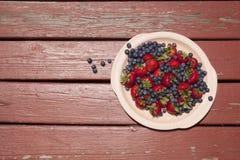 Uppläggningsfat av jordgubbar med blåbär som över spiller på en Rus royaltyfri bild