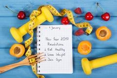 Upplösningar för det nya året som är skriftliga i anteckningsbok på blått, stiger ombord Arkivfoton