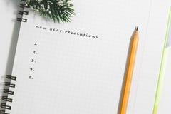 Upplösningar för nytt år, anteckningsbok och gul blyertspenna med barrträdbr Arkivfoton