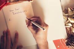 Upplösningar för nytt år som är skriftliga med en hand på anteckningsboken med deco för nya år Royaltyfria Bilder