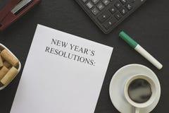 Upplösningar för ` s för nytt år skyler över brister, en kopp för vitt kaffe med tefatet och brevpapper Royaltyfri Fotografi