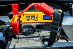 uppladdning av en bil med elektricitet till och med kablar fr?n ett kompakt batteri royaltyfri foto