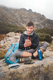 Uppladdning av en mobiltelefon på en bergslinga arkivbilder