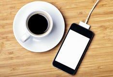 Uppladdningsbar smartphone och en kopp av espresso Royaltyfri Fotografi