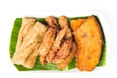 Uppläggningsfat av den stekte bananen, stekte sötpotatisar och fiskklumpar Arkivfoto