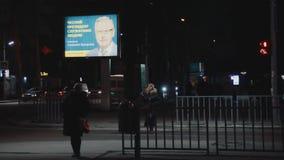 Upplyst affischtavla Annonsering av valkampanjen av presidentkandidaten Anatoly Gritsenko Tempel på solnedgången övergångsställe lager videofilmer