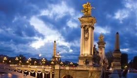 Upplyst Alexander som thirden överbryggar och Seine på natten i Par Arkivfoto