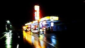 Upplyst bensinstation i regnig nattver 1 royaltyfria foton