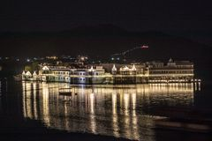 Upplyst buidling och fartyg över sjön Picholla, Udaipur, rajor Fotografering för Bildbyråer