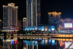 Upplyst flodstrand för modern ljus natt med commercailbyggnader och reflexioner Arkivbild