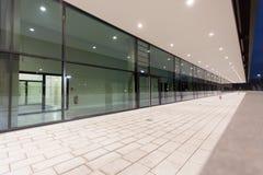 Upplyst fot- passageperspektiv längs glass byggnad Arkivfoto