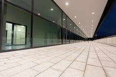 Upplyst fot- passageperspektiv längs glass byggnad Arkivbild