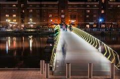 Upplyst fotbro in över den norr skeppsdockan i Canary Wharf vid natt Fotografering för Bildbyråer