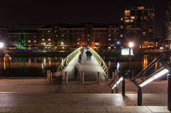 Upplyst fotbro in över den norr skeppsdockan i Canary Wharf vid natt Royaltyfri Bild