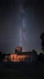 Upplyst kyrka med natthimmel för mjölkaktig väg under den Perseid meteorregnet Royaltyfri Fotografi